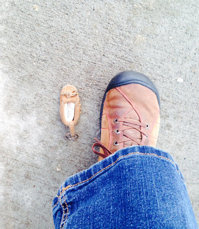 Tiny moccasin keychain abandoned in snow.