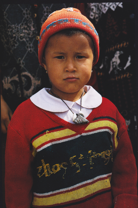 child wearing hat, sweater and amulet necklace